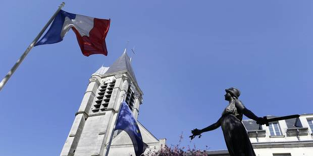 The steeple of the Saint-Cyr and Sainte-Julitte church is seen behind a French national flag (L) and a flag of Europe on April 22, 2015, in Villejuif, outside Paris. This church was probably a target of Sid Ahmed Ghlam, a student suspected of planning to attack a church in France, who was arrested on April 19, 2015. French police found Arabic documents mentioning the Islamic State group and Al-Qaeda at his home, the Paris prosecutor said on April 22. The 24-year-old Franco-Algerian's plans were exposed purely by chance after he called an ambulance over a bullet injury to his leg. Police traced a trail of Sid Ahmed Ghlam's blood to his car, where they discovered an arsenal of weapons, Interior Minister Bernard Cazeneuve told reporters. AFP PHOTO / KENZO TRIBOUILLARD