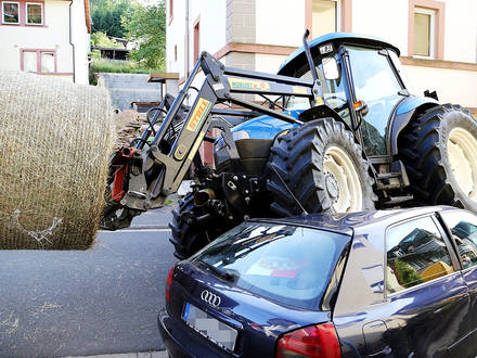 A tractor rests with two wheels on a car in Rothenbuch, Germany, 10 July 2013. The 82 year-old driver of the tractor that was transporting a bale of hay misjudged the distance to a parked car and drove onto it. The tractor wasn't damaged but the car was totaled. Photo: RALF HETTLER Reporters / DPA