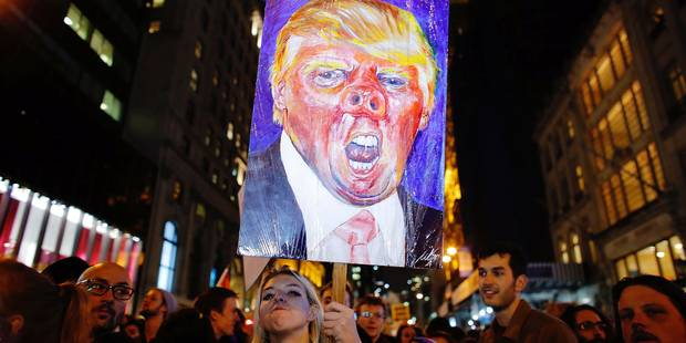 TOPSHOT - A woman holds a poster as she takes part in a protest against President-elect Donald Trump in New York City on November 9, 2016. / AFP PHOTO / KENA BETANCUR
